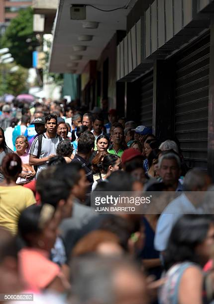 People line up to buy basic food and household items outside a supermarket in Caracas Venezuela on January 21 2016 Trade unions demonstrated...