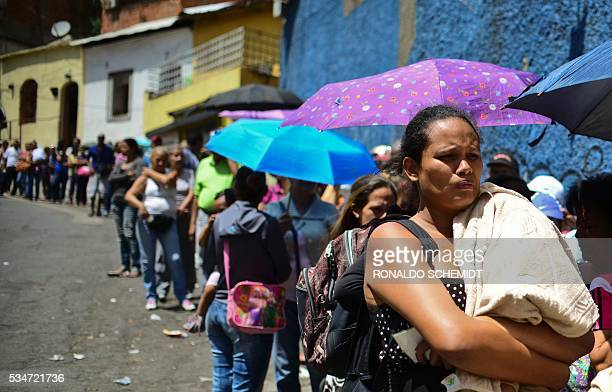 People line up to buy basic food and household items outside a supermarket in the poor neighborhood of Lidice in Caracas Venezuela on May 27 2016 /...