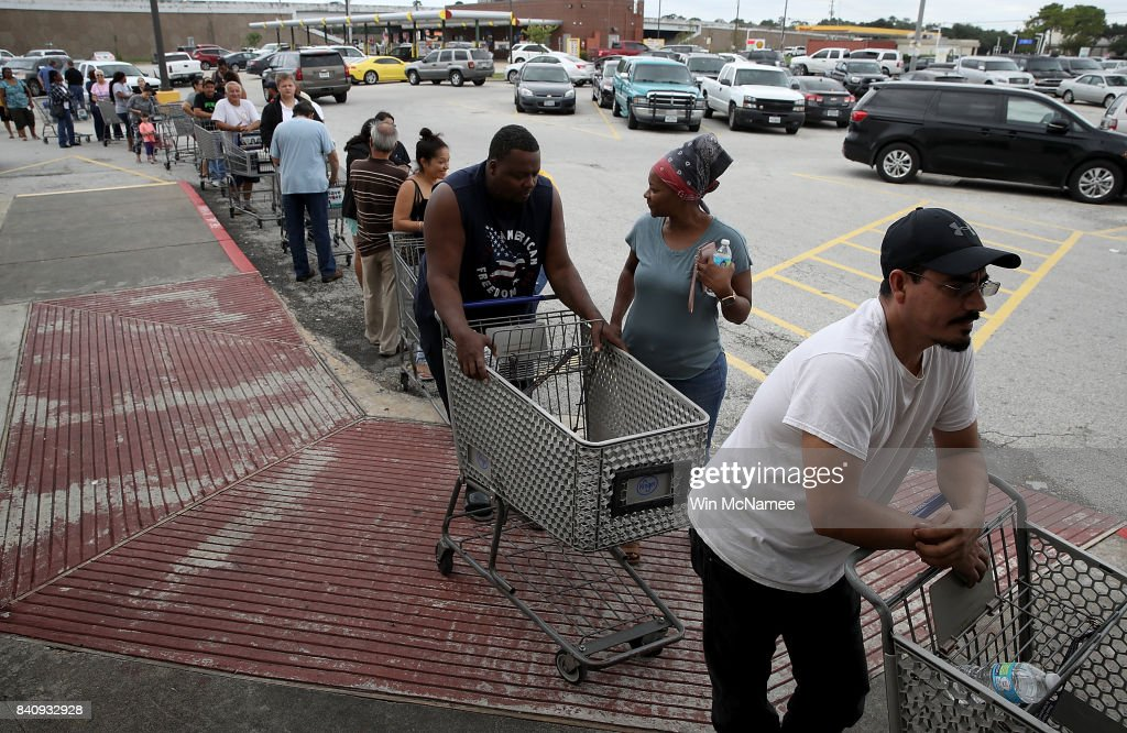 People line up to buy groceries in the Chanelview section of Houston as flood waters began to recede following Hurricane Harvey August 29, 2017 in Houston, Texas. The city of Houston is still experiencing severe flooding in some areas due to the accumulation of historic levels of rainfall, though the storm has moved to the north and east.