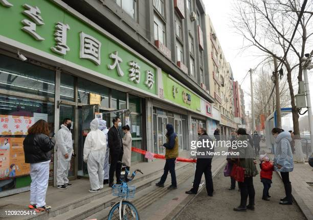 People line up to buy protective masks at a pharmacy on February 27, 2020 in Hohhot, Inner Mongolia Autonomous Region of China.