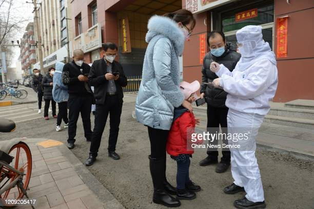 People line up to buy protective masks at a pharmacy on February 27 2020 in Hohhot Inner Mongolia Autonomous Region of China