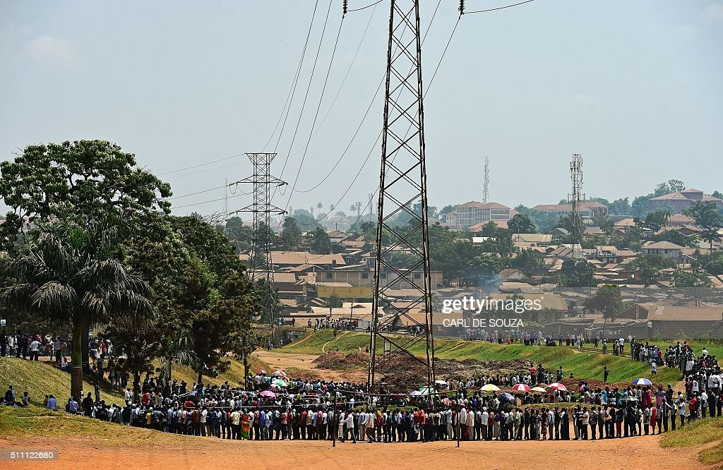 TOPSHOT - People line up to cast their vote in presidential and parliamentary polls, on February 18, 2016 at the Nasuti polling station in Mukono District, some 23 kilometres east of the capital Kampala. Ugandans began voting on February 18 in presidential and parliamentary polls, with veteran leader Yoweri Museveni widely expected to extend his power into a fourth decade. / AFP / CARL