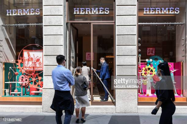 People line up to enter a Hermes luxury shop on May 18 2020 in central Milan during the country's lockdown aimed at curbing the spread of the COVID19...