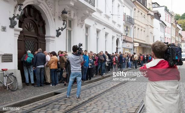 People line up to enter the regional court in Freiburg southern Germany on September 5 2017 to attend the trial that starts against Husseen K who is...