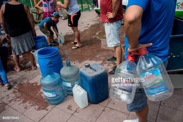 People line up to get water during a drinking water supply cut in Santiago on February 26 2017 More than 14 million homes in Santiago were affected...