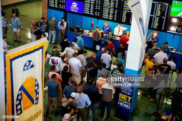 People line up to place their wagers on June 14 2018 at the Monmouth Park Sports Book on the first day of legal sports betting in the state in...