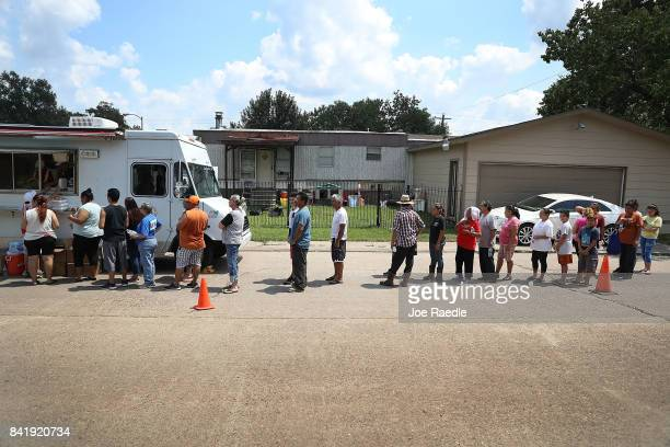People line up to receive food and water from a Salvation Army truck after their homes were inundated with flood waters during Hurricane and Tropical...
