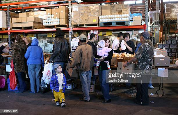 People line up to receive food for a Thanksgiving meal November 24 2009 at the Alameda Food Bank in Alameda California Hundreds of needy people lined...