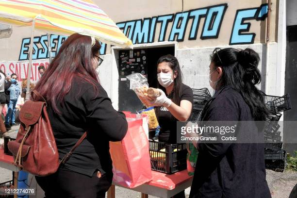 People line up to receive parcels of food and basic necessities in Quarticciolo on May 09 2020 in Rome Italy Young volunteers have organised a...