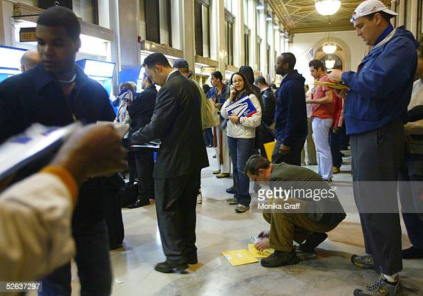 People line up to use the automated postage kiosks as hundreds visit the James A Farley post office to mail their tax returns before the midnight...