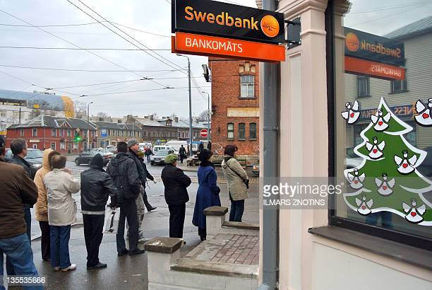 People line up to withdraw cash at a Swedbank automatic teller machine in Riga on December 12 2011 More than 100 cashpoints in Latvia had run out of...