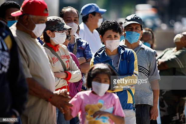 People line up wearing surgical masks to prevent contracting the swine flu as they wait to see a doctor at a mobile health clinic on May 1 2009 in...