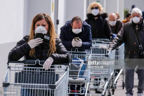 People lined up at the supermarket with a grocery cart all wearing masks for fear of Coronavirus infection