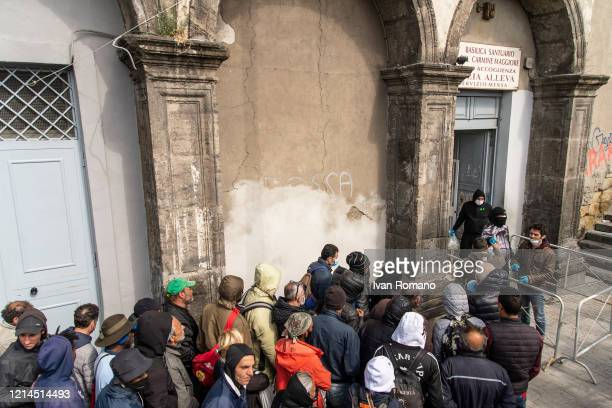 People lined up while wait to receive a meal at the soup kitchen of the Father Elia Alleva Hospitality Center of the Basilica Santuario del Carmine...