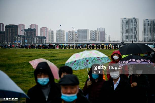 People line-up to undergo Covid-19 coronavirus tests at a makeshift testing center in Tianjin on November 21 after new coronavirus cases were...