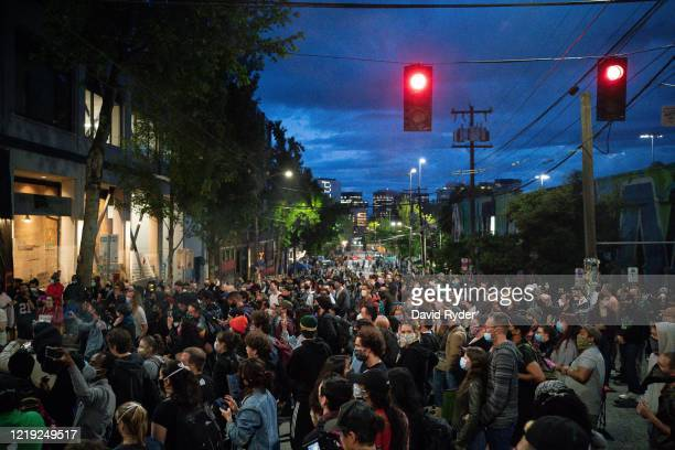 People listen as a band plays a free show in front of the Seattle Police Departments East Precinct in the socalled Capitol Hill Autonomous Zone on...
