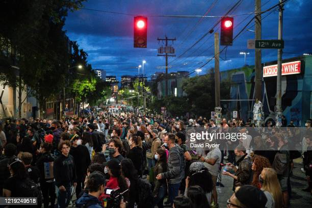 "People listen as a band plays a free show in front of the Seattle Police Departments East Precinct in the so-called ""Capitol Hill Autonomous Zone"" on..."