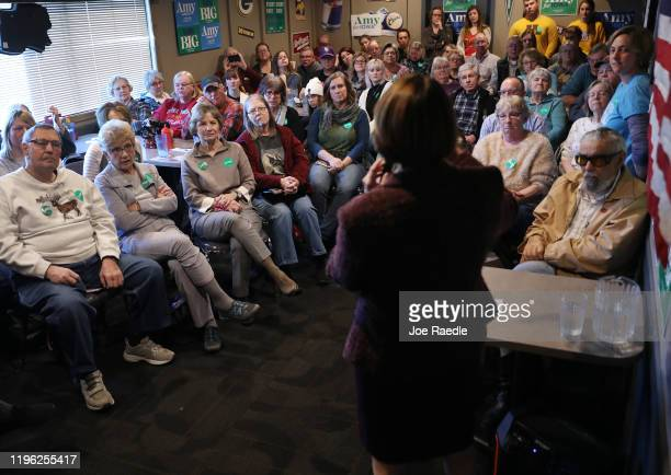 People listen as Democratic presidential candidate Sen Amy Klobuchar speaks during a campaign stop at Miller's Sports Bar and Restaurant on December...