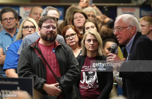 People listen as Democratic presidential candidate Sen. Bernie Sanders speaks during a stop at a campaign field office on February 02, 2020 in West...