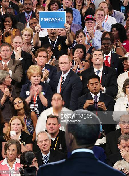 People listen as Democratic presidential candidate US President Barack Obama speaks on stage as he accepts the nomination for president during the...