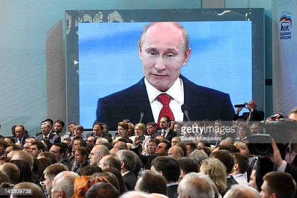 People listen as projected on a screen Russian President Vladimir Putin speaks during a United Russia party congress to elect Russian Prime Minister...