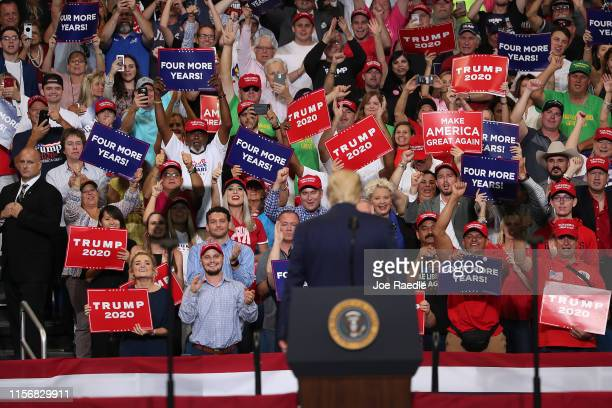 People listen as US President Donald Trump speaks during his announcement of his candidacy for a second presidential term at the Amway Center on June...