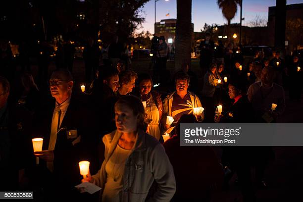 People listen during a candlelight vigil held at the San Bernardino County Board of Supervisors headquarters in San Bernardino CA on Monday December...