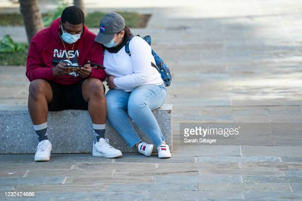 People listen on a cell phone to the verdict of the Derek Chauvin trial at Black Lives Matter Plaza near the White House on April 20, 2021 in...