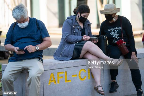 People listen on cell phones to the verdict of the Derek Chauvin trial at Black Lives Matter Plaza near the White House on April 20, 2021 in...