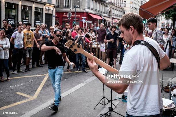 People listen to a band performing on June 21 2015 in a street of Lyon eastern France as part of the 34rd edition of the annual music event 'La Fete...