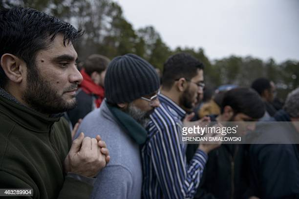 People listen to a funeral prayer during a burial February 12 2015 in Wendell North Carolina More than 5000 people gathered for the funeral of Deah...