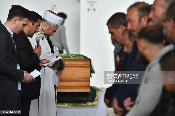 People listen to a Muslim prayer next to the coffin of a boy who was killed on June 9 by a driver without a driving license during a funeral ceremony...