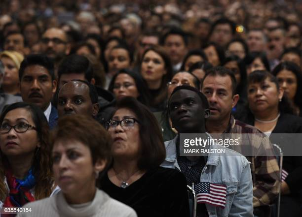 TOPSHOT People listen to a speech before pledging allegiance to the United States of America as they receive US citizenship at a naturalization...