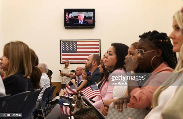 People listen to a taped broadcast of President Donald Trump as they participate in a ceremony to become American citizens during a US Citizenship...