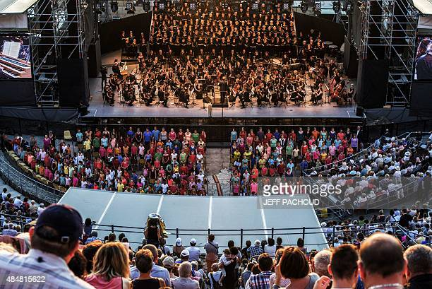 People listen to an orchestra playing the Te Deum composed by Hector Berlioz on August 21 2015 in Vienne theater during a concert part of the annual...