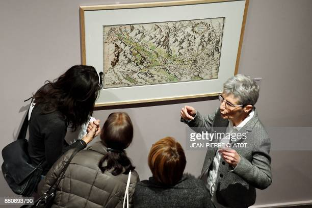 People listen to explanations from a guide as they visit the exhibition 'Les Alpes de Jean de Beins Des cartes aux paysages ' at the Ancien Eveche...