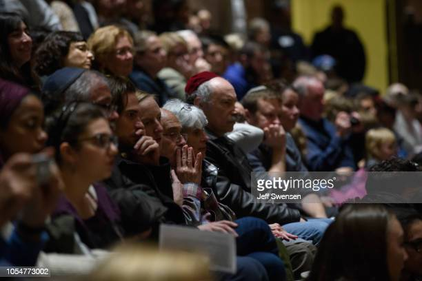 People listen to interfaith speakers at the Soldiers and Sailors Memorial Hall before a service to honor and mourn the victims of Saturday's mass...