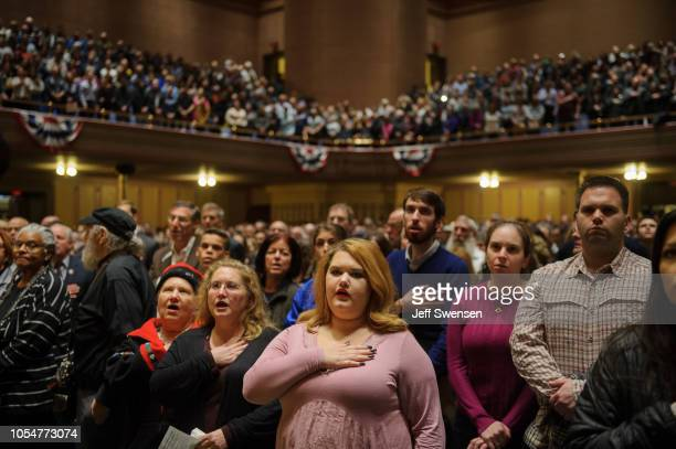 People listen to interfaith speakers at the Soldiers and Sailors Memorial Hall during a service to honor and mourn the victims of Saturday's mass...