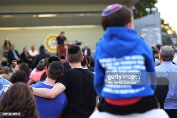 People listen to Joseph Borgen, a recent victim of a hate crime, speak during a rally denouncing anti-Semitic violence on May 27, 2021 in Cedarhurst,...