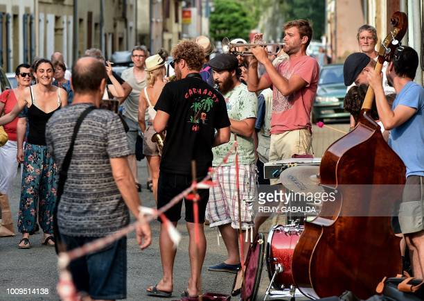 People listen to musicians performing in a street of Marciac on July 31 during the 41st edition of the Marciac Jazz Festival