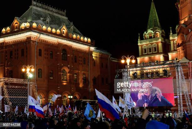 TOPSHOT People listen to presidential candidate President Vladimir Putin during a rally and a concert celebrating the fourth anniversary of Russia's...