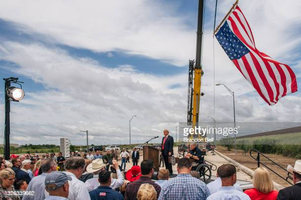 People listen to Texas Gov. Greg Abbott's address during a tour to an unfinished section of the border wall on June 30, 2021 in Pharr, Texas. Gov....