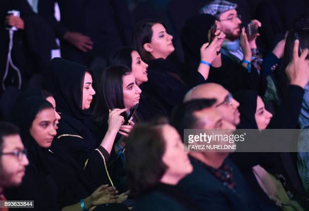 People listen to US actor John Travolta speaking during a panel discussion at the Apex Convention Center in the Saudi capital Riyadh on December 15...