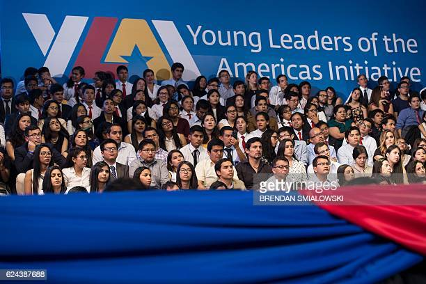 People listen to US President Barack Obama speaking during a Young Leaders of the Americas Initiative town hall meeting at the Pontifical Catholic...