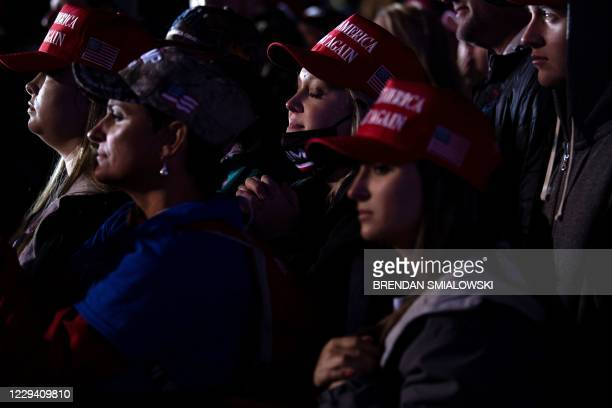 People listen while US President Donald Trump speaks during a Make America Great Again rally at Richard B. Russell Airport in Rome, Georgia on...