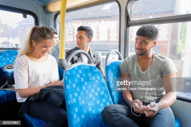 People listening to earbuds on bus