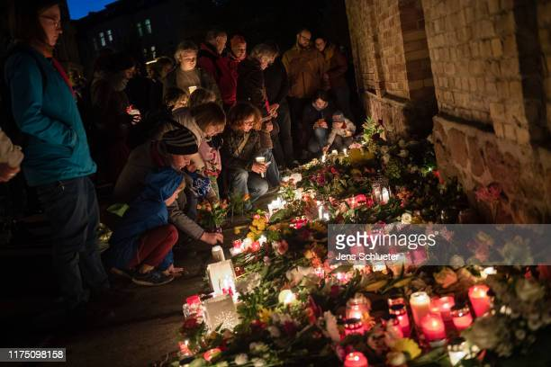 People lit candles as they mourn in front of the entrance to the Jewish synagogue on October 10 2019 in Halle Germany Law enforcement authorities...