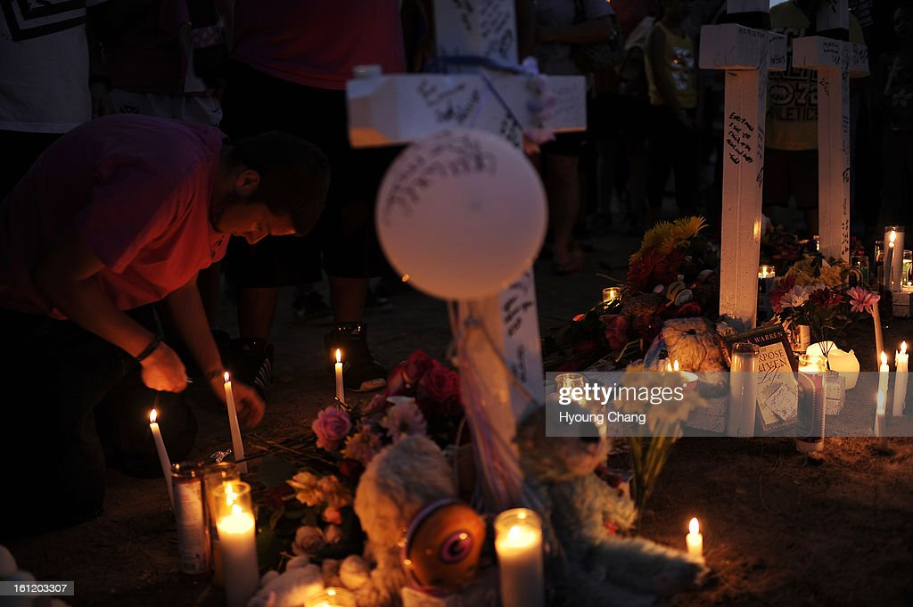 People lit candles for the memorial for shooting victims at