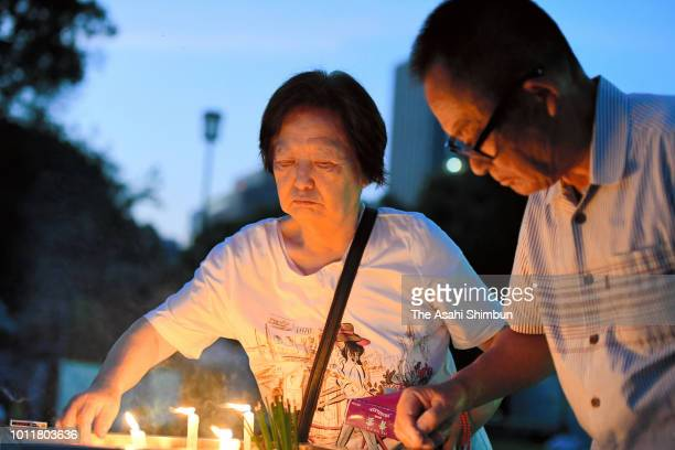 People lit candles to pray for the victims prior to the Peace Memorial Ceremony at the Peace Memorial Park on the 73rd anniversary of the Hiroshima...