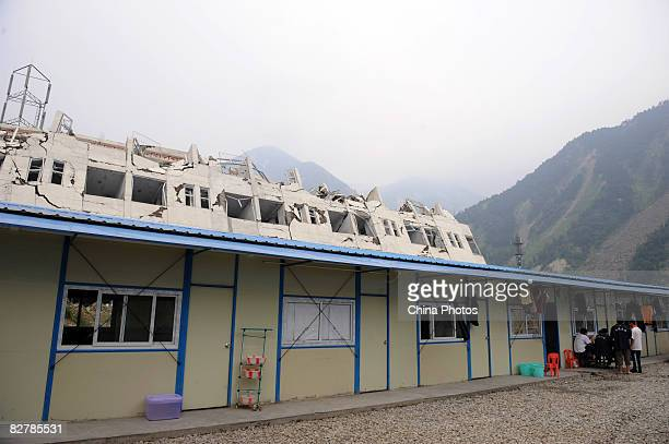 People live in prefabs in front of the damaged buildings of the Xuankou Middle School at Yingxiu Township on September 11 2008 in Wenchuan County of...